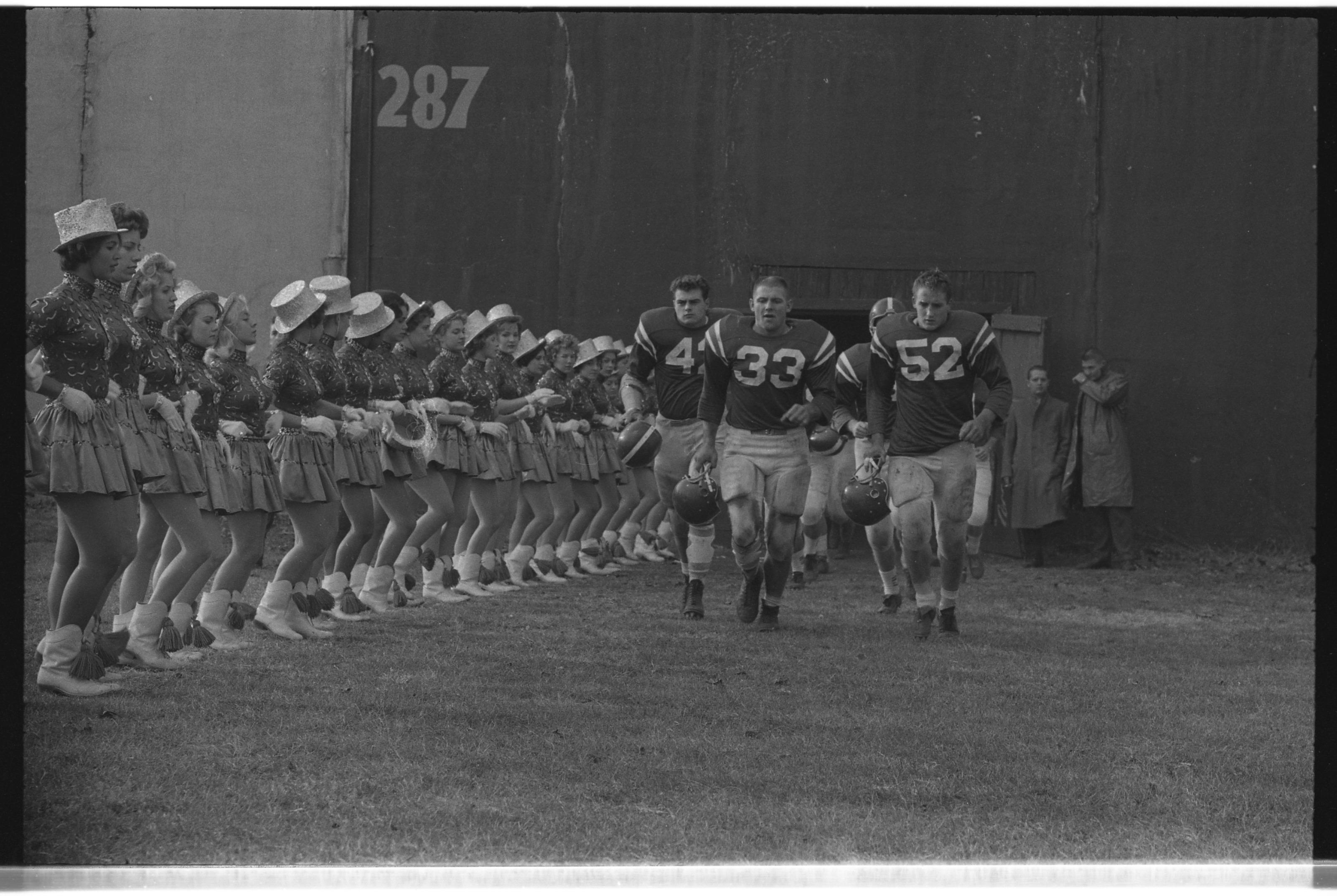 Football players enter stadium, running past Sparkettes