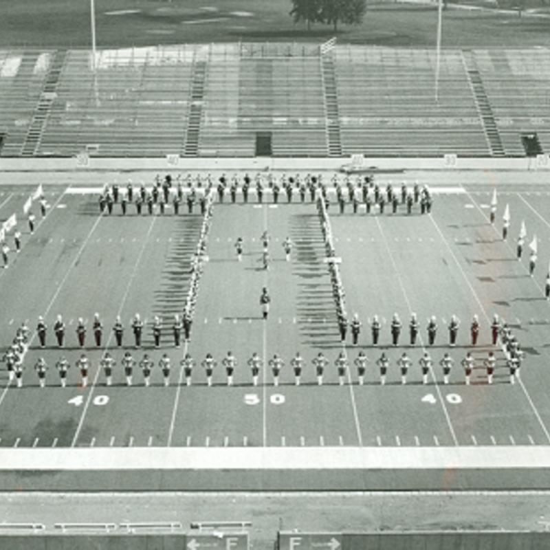 "Marching band in ""I"" formation at empty football field, no date"