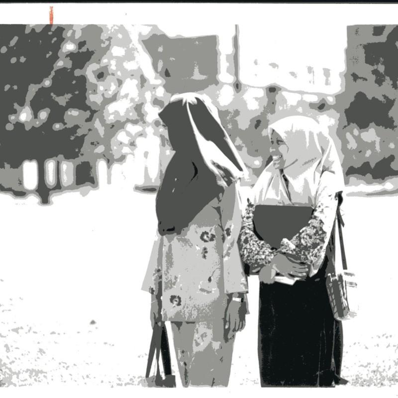 [Women walk around campus]