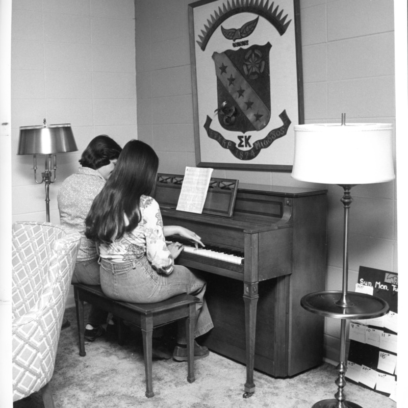 Sorority sisters playing piano in Residence hall